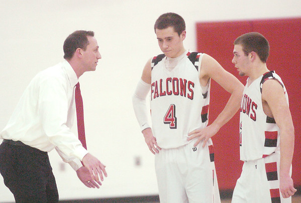 WARREN DILLAWAY / Star Beacon<br /> JEREMY HUBER, Jefferson basketball coach, talks to Falcons Jeremy Bloom (4) and Jacob Hamilton on Tuesday during a home game with Lake Catholic.
