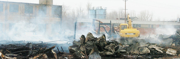 WARREN DILLAWAY / Star Beacon<br /> HEAVY EQUIPMENT is used to sift through the remnants of the former General Alumninum building on Tuesday morning after it burned Monday night in Conneaut.