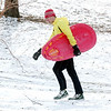 WARREN DILLAWAY / Star Beacon<br /> JEREMIAH ALLEN, 16, of Geneva, walks back up a Lake Shore Park hill while sledding on Monday afternoon in Ashtabula Township.