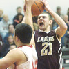 WARREN DILLAWAY / Star Beacon<br /> QUINTIN RATLIFF (21) of Pymatuning Valley drives to the basket with Ron Varckette of Geneva defending on Tuesday night at Geneva.