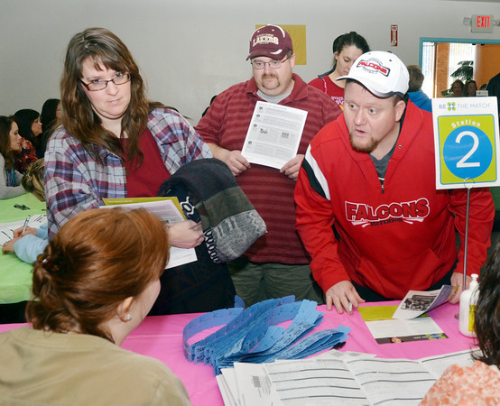 WARREN DILLAWAY / Star Beacon<br /> BRYAN HAGERDON (right) of Jefferson and Allison (right) and Mark Limestool (center), both of Andover, get instructions from Tonya Davis (back to camera) on Saturday during a bone marrow drive at the Jefferson Community Center.