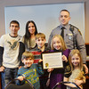 WARREN DILLAWAY / Star Beacon<br /> OHIO STATE Highway Patrol Trooper Brandon Miller (left) received a certificate honoring his lifesaving work on Februry 4 in Harpersfield Township. He received the  citation from Captain Chris J. Zurcher who is the Cleveland District Commander. Miller is surrounded by his family (from left front row) Benjamin, 5; Jacob, 12, Julianna, 9, Gabriella, 6, and (from left second row) John, 17 his wife Chris and Miller.
