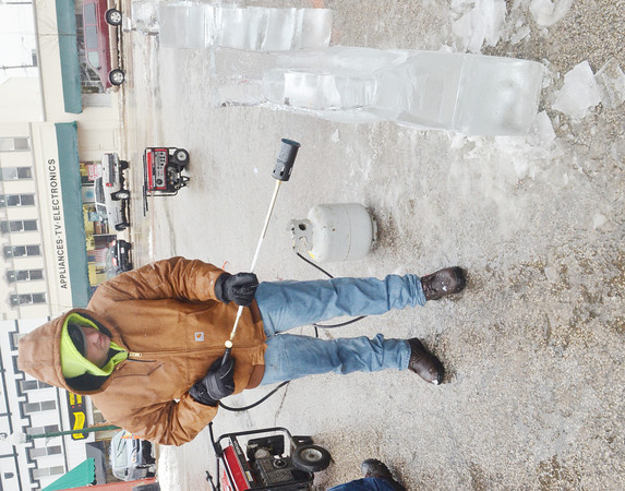 WARREN DILLAWAY / Star Beacon<br /> RYAN TRIBUZI puts the finishing touches on an ice sculpture on Saturday afternoon at Winterfest in downtown Geneva.