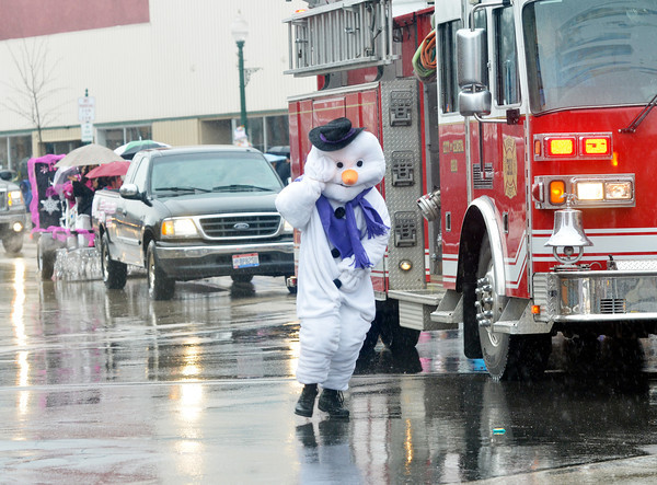 WARREN DILLAWAY / Star Beacon<br /> LAKE EFFECT Louis braves rainy weather during the Winterfest Parade on Saturday in downtown Geneva.