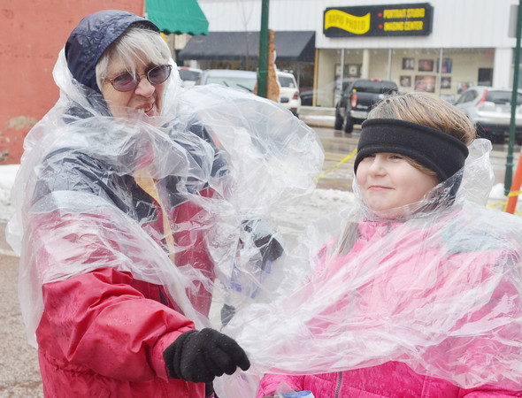 WARREN DILLAWAY / Star Beacon<br /> SANDY LEONARD (left) of Ashtabula and Telia Pursley, 9, also of Ashtabula, try to stay dry during Winterfest in downtown Geneva on Saturday afternoon.