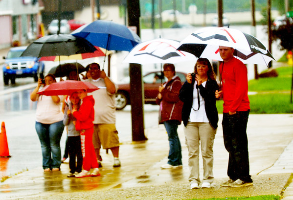 WARREN DILLAWAY / Star Beacon<br /> PARADE WATCHERS try to stay dry along Main Avenue during the Multi-Cultural Festival in downtown Ashtabula on Saturday.