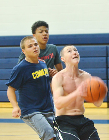 WARREN DILLAWAY / Star Beacon<br /> MICHAEL MIRANDO (with ball) drives to the hoop with Troy Colucci (left) and Jacob Spees (far back) in close pursuit during a Conneaut open gym marathon fund raiser on Saturday at the Conneaut Middle School.