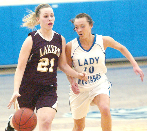 WARREN DILLAWAY / Star Beacon<br /> GEENA GABRIEL (21) of Pymatuning Valley dribbles to the basket with Grand Valley's Kelly Preske close behind on Thursday evening in Orwell.