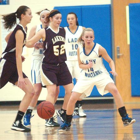 WARREN DILLAWAY / Star Beacon<br /> ABBY HAMILTON (with ball) of Pymatuning Valley dribbles across court with Grand Valley's Chelsea Stehlik (14) defending and Laker Heather Brant (52) in the background with Mustang Kelly Preske (10).