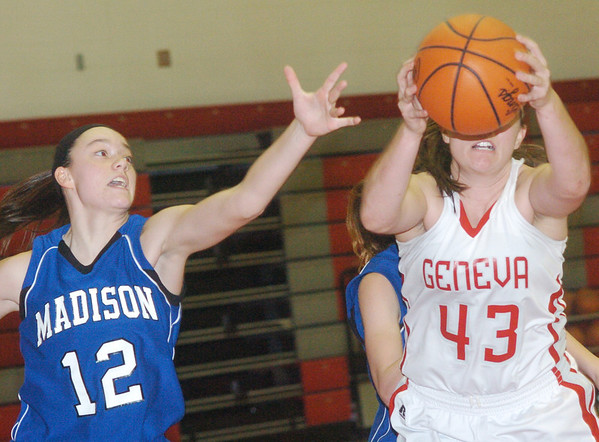 WARREN DILLAWAY / Star Beacon<br /> TAYLOR GUSTIN (12) of Madison reaches for the ball as Geneva' Natalie Thomas grabs a rebound on Saturday afternoon at Geneva.