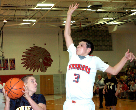 WARREN DILLAWAY / Star Beacon<br /> AMEN GERICS (with ball) of Conneaut prepares to shoot as Edgewood's Connor McLaughlin leaps for the block on Friday night at Edgewood.