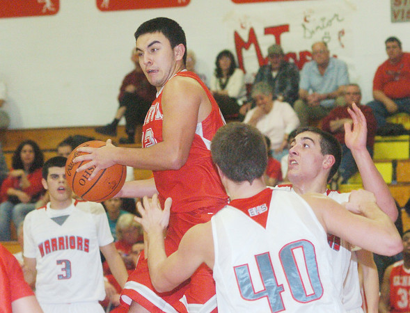 WARREN DILLAWAY / Star Beacon<br /> RON VARCKETTE (with ball) of Geneva leaps for a rebound between Edgewood's Connor McLaughlin 93), Andrew Konczal (40) and Matt Fitchet (right facing) on Tuesday night at Edgewood.