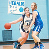 WARREN DILLAWAY / Star Beacon<br /> MACKENZIE STENROOS (12) of St. John tries to get by Katie Futty of Grand Valley on Saturday during a game at Mahoney Gymnasium in Ashtabula.