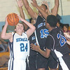 WARREN DILLAWAY / Star Beacon<br /> ZACH TAYLOR of St. John tries to shoot the ball as St. Martin de Porres defenders Darious Smith (15) and Darrin Gouch leap for the block on Saturday at Mahoney Gymnasium in Ashtabula.