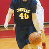 WARREN DILLAWAY / Star Beacon<br /> CHRISTIAN WILLIAMS of Conneaut dribbles up court with Geneva's David Smalley close behind on Tuesday night at Geneva.