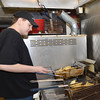 WARREN DILLAWAY / Star Beacon<br /> MTICHELL KIBLER prepares food at Chops in Harpersfield Township on Tuesday morning in preparation for New Year's Eve customers.