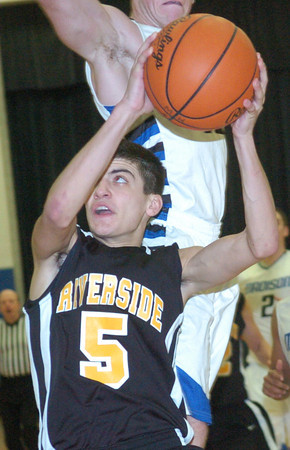 WARREN DILLAWAY / Star Beacon<br /> BRAD RINELLA (5) of Riverside drives to the basket in front of Aaron Petrucelli of Madison attempts the block on Friday night at Madison.