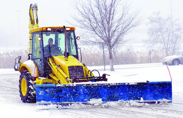 A SNOW plow clears the Super Kmart parking lot in Ashtabula Township last December.