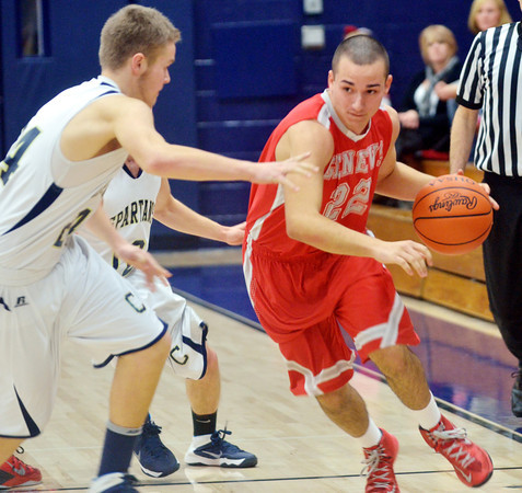 WARREN DILLAWAY / Star Beacon<br /> ALEX FISTEK (22) of Geneva tries to drive by Marcus Barrickman (24) of Conneaut on Tuesday night at Garcia Gymnasium in Conneaut.