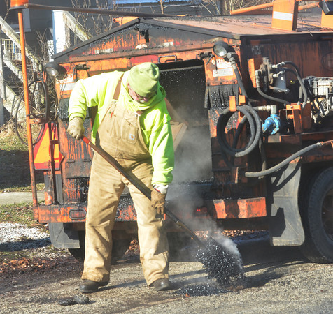 WARREN DILLAWAY / Star Beacon<br /> MARVIN KEEN fills pot holes on Strong Avenue  in Ashtabula on Tuesday afternoon.