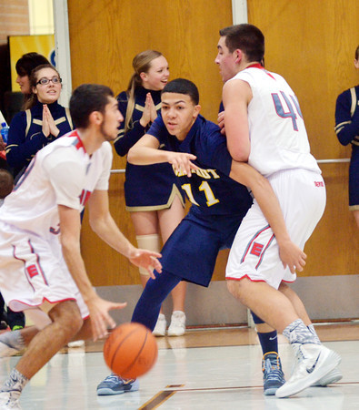 WARREN DILLAWAY / Star Beacon<br /> JAKE SPEES (11) of Conneaut tries to get through a pick set by Matt Fitchet of Edgewood (right) while Eli Kalil of Edgewood dribbles on Friday night at Edgewood.