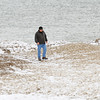 WARREN DILLAWAY / Star Beacon<br /> STEVE TAYLOR of Geneva-on-the-Lake walks along ice mounds with open water of Lake Erie in the background on Friday at Geneva State Park.