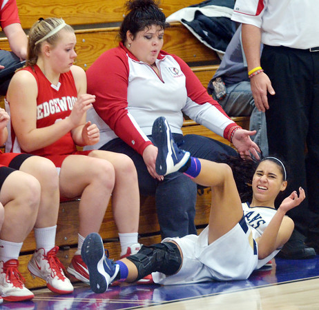 WARREN DILLAWAY / Star Beacon<br /> ALYSSA CHADWICK of Conneaut ends up diving into the Edgewood bench after diving for a loose ball on Saturday afternoon at Garcia Gymnasium in Conneaut.