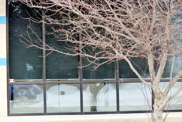 WARREN DILLAWAY / Star Beacon<br /> A PEDESTRIAN (far left)is reflected in the window of a Route 20 building in Conneaut on Tuesday morning.