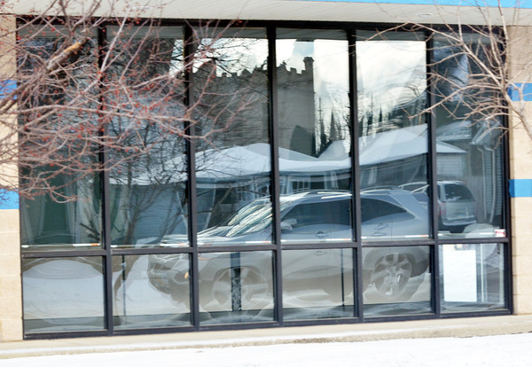 WARREN DILLAWAY / Star Beacon<br /> A CAR is reflected in the window of a business on Route 20 in Conneaut on Tuesday morning.