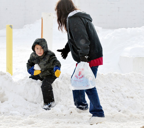 WARREN DILLAWAY / Star Beacon<br /> JEVANTE BRADLEY, 5, is helped over a pile of snow along Main Avenue in Ashtabula on Friday afternoon by his aunt Stacey Snyder, both of Ashtabula.