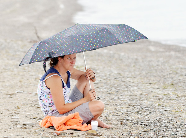 WARREN DILLAWAY / Star Beacon<br /> KRIS HOLLAND of Steubenville tries to stay dry during  a rain storm that appeared quickly over Lake Erie at Conneaut Township Park beach on Wednesday afternoon.