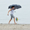 WARREN DILLAWAY / Star Beacon<br /> KRIS HOLLAND of Steubenville races to rescue clothes from a rain storm that appeared quickly over Lake Erie at Conneaut Township Park beach on Wednesday afternoon.