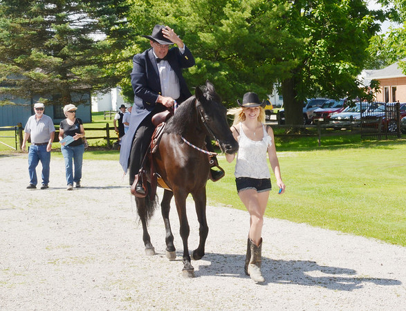 WARREN DILLAWAY / Star Beacon<br /> REV. VERNON PALO, of the Andover United Methodist Church, mounts a horse, Lena, with the help of Misty Heavner of Jefferson during an 1890 Re-Enactment on Saturday at the Jefferson Depot Village.