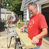 WARREN DILLAWAY / Star Beacon<br /> DANA QUINN of Conneaut measures a board while building a handicap ramp at a Madison Street home in Conneaut on Tuesday. The Loving Equally All Families volunteers are working on 50 projects throughout the city.