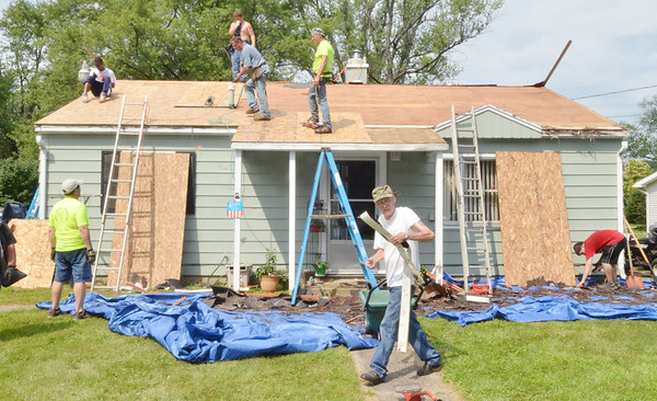 WARREN DILLAWAY / Star Beacon<br /> DONALD CHAMPLIN (center) carries a gutter while Loving Equally All Families volunteers make a roof for the man who has significant medical problems.
