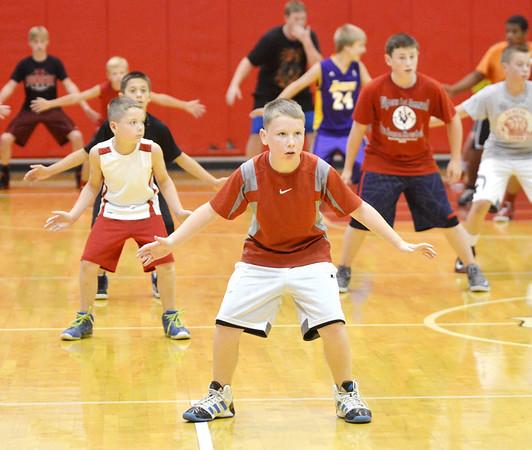 WARREN DILLAWAY / Star Beacon<br /> KENLEY CUNNINGHAM (foreground center) and fellow Geneva Basketball Camp participants work on defense drills on Tuesday at Geneva High School.