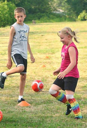 WARREN DILLAWAY / Star Beacon<br /> PAULINE FORMAN, 9, (right) and Donovan Leininger, 10, participate in a drill during Jefferson Soccer Camp on Tuesday evening in Jefferson.