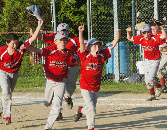 WARREN DILLAWAY / Star Beacon<br /> COLE OPALKO (center middle), Clayton Queen (middle front) and Caleb Nugent (far left) lead a group of Minor League All Stars in celebration after defeating Conneaut in a District 1 championship game on Thursday night at Carraher Field in Geneva.