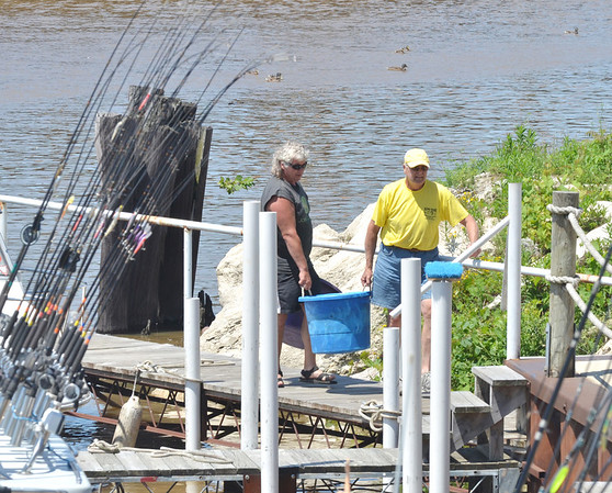 WARREN DILLAWAY / Star Beacon<br /> TOM HOGAN (right), a captain of the Kona Babe, helps a customer carry fish to a cutting station in Ashtabula.