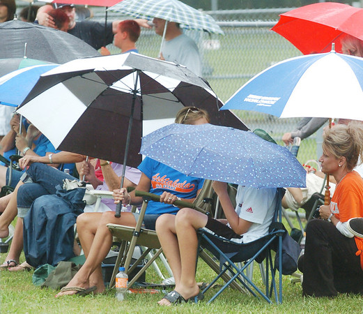 WARREN DILLAWAY / Star Beacon<br /> ASHTABULA MAJOR League All Star fans try to stay dry on Monday afternoon during state tournament action at Cederquist Park in Ashtabula.