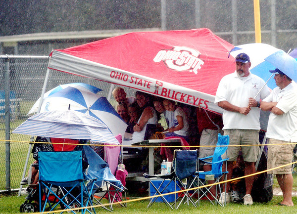 WARREN DILLAWAY / Star Beacon<br /> AVON LITTLE League fans try to stay dry during a thunder storm on Tuesday afternoon at the state tournament at Cederquist Park in Ashtabula.