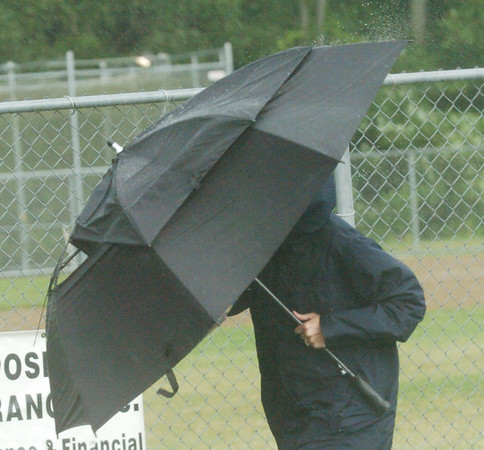WARREN DILLAWAY / Star Beacon<br /> MICHELLE WOOD of Washington Court House tries to stay dry during a thunderstorm at Cederquist Park on Tuesday afternoon in Ashtabula. Wood was in town for the Little League State Tournament.