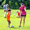 WARREN DILLAWAY / Star Beacon<br /> BECKA JACKAM, of the Geneva Middle School soccer team, instructs Nathan Cunningham, 4, of Geneva during the Mike Mikulin Memorial Soccer Camp in Geneva on Tuesday evening.