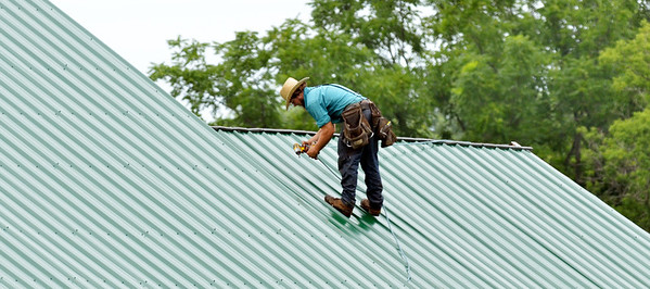 WARREN DILLAWAY / Star Beacon<br /> AN AMISH roofer works along Route 84 in Kingsville Township on Tuesday afternoon.