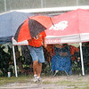 WARREN DILLAWAY / Star Beacon<br /> A WHEELERSBURG Little League fan tries to stay dry during a thunder storm on Tuesday afternoon at the state tournament at Cederquist Park in Ashtabula.