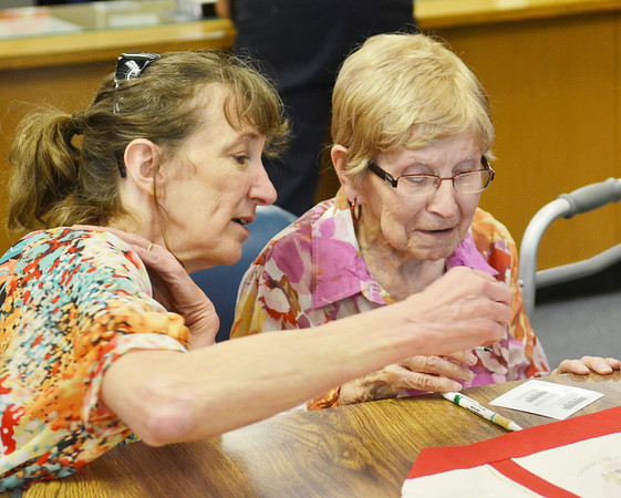 WARREN DILLAWAY / Star Beacon<br /> DOROTHY ANDRUS VASBINDER, who turns 100 years old today, prepares to sign her honorary library card at the Kingsville Public Library on Friday afternoon. Vasbinder's great, great niece Joann Burton helped her in the process.