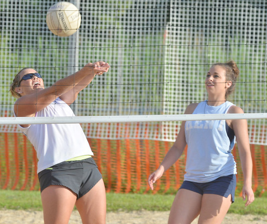 WARREN DILLAWAY / Star Beacon<br /> SHELLY MILLER of the Lethal Ladies sets the ball as teammate Brittany Wentworthwatches during the Softball City Sand Volleyball League Tuesday evening. The Fab 4 clinched the championship with a win over the Lethal Ladies.