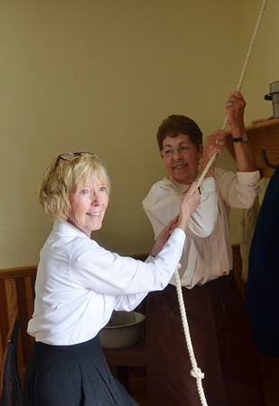 WARREN DILLAWAY / Star Beacon<br /> NANCY HODGE (left) and Marilyn Johnson ring the bell at the recently completed 1855 Wayne School House replica at the Ashtabula County Antique Engine Club grounds in Wayne Township.