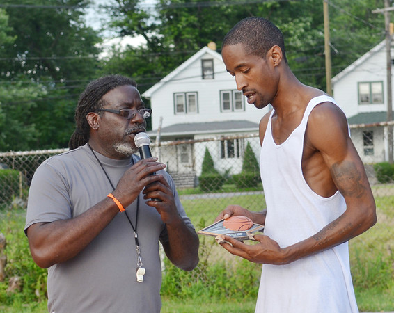 WARREN DILLAWAY / Star Beacon<br /> MICHAEL OSBORNE, West Side Shootout tournament director, presents Anthony Hargrove with the slam dunk trophy on Friday night at the West Avenue courts in Ashtabula.