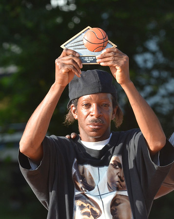"""WARREN DILLAWAY / Star Beacon<br /> ERICH """"WHITEHEAD"""" HUNT displays his trophy after winning the West Side Shootout three point shooting contest Friday night at the West Avenue courts in Ashtabula."""